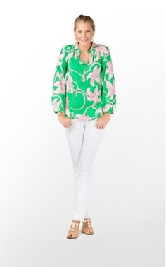 Model wears jade green soft pink hibiscus print flowing longsleeved blouse with banded collar and sleeves, white slimfit jeans, accessorized with gold sandals.