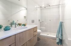 The bathroom was completely remodeled and features large glass tiles that read as one single surface material. The floors are made up of unfinished poured concrete.