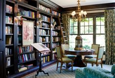 traditional home library with wall of bookshelves, round table for dining or working, comfy reading chairs