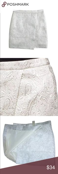 NWT J. Crew Origami Skirt In Metallic Matelassé NWT J. Crew Origami Skirt In Metallic Matelassé SIZE 6 - Price on tag is $110  I try my very best to capture the correct color/shade.  The actual shade may vary in person.  Textured paisley design Silvery sheen color Faux wrap style Asymmetric front flap and wide seamed hem Flat waistband and back darts for fit Concealed back zip fastening with hook and eye secure Fully Lined 54% Polyester, 30% Cotton, 16% Metallic Fiber Waist: 32 inches around…