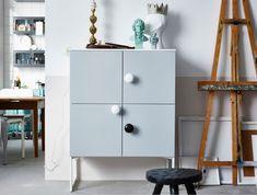 Ein Schrank gestaltet aus weißen Küchenschränken, VEDDINGE Türen in Grau und weißen Beinen.