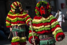 """Performers from the Portuguese village of Podence dressed in a traditional costume during annual carnival festivities on February 26, 2017, in Macedo de Cavaleiros, Portugal. Revelers, known as """"Caretos"""" wear brass or wooden masks and dress up in costumes made of dyed wool and with cowbells in their belts."""