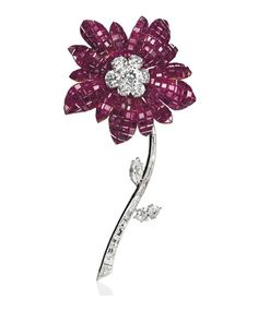 A RUBY AND DIAMOND 'MAGNOLIA' BROOCH, BY VAN CLEEF & ARPELS   The flowerhead with mystery-set ruby petals and brilliant-cut diamond pistil, to the detachable baguette-cut and marquise-shaped diamond stem and leaves, 1968, 10.0 cm, with French assay marks for platinum and gold  Signed Van Cleef & Arpels, no. 18.979