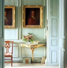 Love the gilded furniture and portrait frames in this entryway.