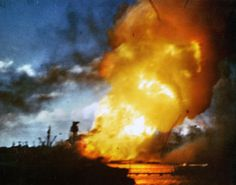 This startling color still frame from a film reel captures the moment the catastrophic explosion doomed the battleship USS Arizona. A Japanese bomb fashioned from a modified artillery shell detonated a forward powder magazine and caused the devastating explosion that killed 1,177 Americans.