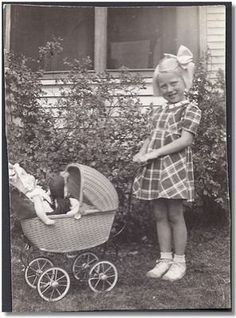 Vintage photo little girl with dolls in doll buggy, circa 1935 - 1950.