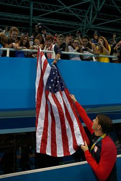 Gold medalist Michael Phelps of the United States is given an American flag by…