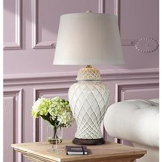 An artful table lamp design in ceramic with an ivory white glaze and a trellis design pattern.