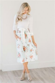 Beautiful dress features a white high neck bodice with 3/4 length sleeves, is follow by a mint and white wide striped skirt with a floral print and has a pretty sewn on waist tie sash and side seam pockets.