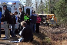 People stand near an ambulance while fire crews investigate a bus Thursday afternoon.