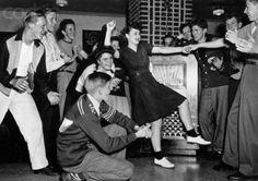 Teenagers rock 'n' rolling around the jukebox, 1950s.