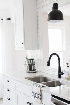 Step Inside The Modern Farmhouse Of Liz Fourez | Glitter Guide. Black farmhouse pendant light, black faucet, black hardware, white Cambria countertops, white cabinets and white subway tile with dark grout lines.