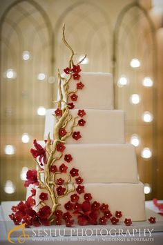Square stacked wedding cake with gold branches, deep red blossoms and orchids.