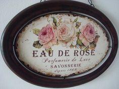"""Cadre plein de charme, il est réalisé en métal, de forme ovale avec une impression """"Eau de roses"""" """"parfumerie de Luxe"""" """"Savonnerie"""" depuis 1868 surmontée de 3 roses, à suspendre à l'aide d'une chaînette. Dimensions : 28 cm x 20 cm avec chaînette 28.5 cm"""
