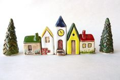 This listing features a whole village of ceramic houses - 5 small ceramic houses and 2 trees for $75.00.  I have hand build these cute houses with love ( no molds or cutters used). Each house is unique and different from each other with lots of little details. After the first fire it is washed with iron oxide to highlight the details of the windows and door and then painted with colorful glazes and fired again in kiln.  My small ceramic houses are wonderful and unique collectibles and…
