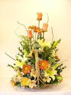 Canasto de coco importado con rosas, lilium y flores silvestres en una armoniosa composición en tonos pasteles.Mide de 70 a 80 cm.