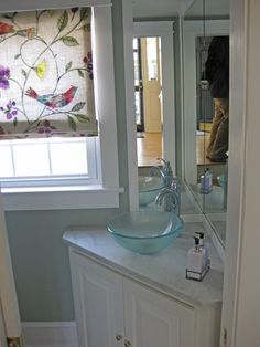 Small powder room bathroom with corner vanity cabinet, mount on top glass bowl sink, and wooden framed mirrors. Bathroom renovation by Sea Island Builders
