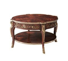 """A mahogany and morado banded cocktail table applied with very fine brass mounts, the brass bound circular top with protruding corners, the frieze with two opposing drawers, on ram""""s head capital cabriole legs joined by an undertier."""