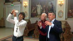 Ron Wood (L) en Charlie Watts (M) van The Rolling Stones worden rondgeleid in de Barokkerk van het Limburgse plaatsje door Camille Oostwegel (R) eigenaar Chateau St. Gerlach.