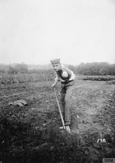 A German disabled soldier learning how to operate a spade with an artificial arm, probably at a school of training for German disabled soldiers at a Westphalian hospital.