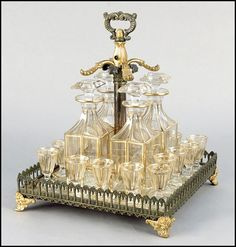 19TH CENTURY FRENCH GILT CRYSTAL AND BRONZE TANTALUS. Unsigned, probably Baccarat. Comprised of a set of four decanters, and sixteen cordials. All contained in a gilt bronze and mirrored stand