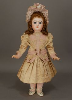 Created after 1890, this twenty-one inch bebe is a product of the Jumeau firm, and is marked E.9.D for Emile Douillet, who was a founding partner in Jumeau et Cie.