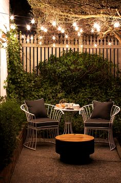 Outdoor string lights cast a lovely glow on this cozy outdoor space at night. The fire pit makes this an exceptional spot for enjoying an evening in the backyard. See more small patio ideas by Aileen Allen of At Home in Love... on The Home Depot Blog. || @aileenallen