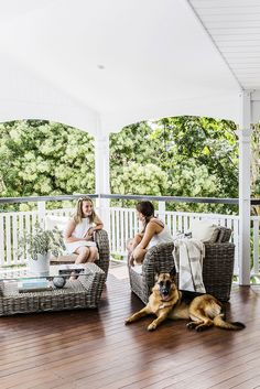 Queenslander: large veranda with timber decking, vaulted roof, white wooden panelling, white railing/balustrade, wicker outdoor furniture