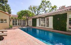 Piscina fica atrás da casa em uma área cheia de verde. Clique na imagem e leia mais sobre decoração de piscina!