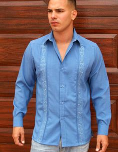 Embroidered Guayabera for men. Linen Look.  Long Sleeve no pockets. Light Blue. - Mexican wedding shirts manufactured by D'accord in the USA. Long Sleeve Button Cuff. These guayaberas feature a unique embroidery all the way from the shoulders to the bottom hem. There are no pockets so as to not interrupt the aesthetics of the embroidery. These embroidered shirts are manufactured on the same pattern as our world class guayaberas. These embroidered long sleeves shirts are elegant and easy care…
