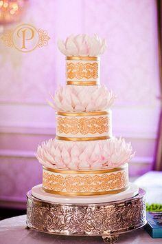 Flower petals beautifully break up these metallic tiers.Cake by Palermo's Bakery