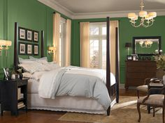 Colorful walls add an unexpected twist to a bedroom with traditional décor. This medium green pairs perfectly with warm whites and dark woods.  Shown: BEHR Hummingbird Green MQ6-48  Related:See how a couple converted their 1950shome's attic into a stylish master suite.