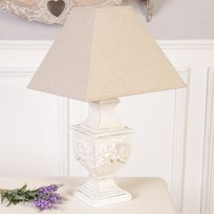 This lamp has a carved wooden base featuring traditional antique design with ornate rose detailing finished with a distressed edging giving this lamp an overall aged feel perfect for adding vintage style to your home. Featuring a large wide trapezoid accompanying linen lamp shade this table lamp is a great addition to any room to add instant vintage style to your home.