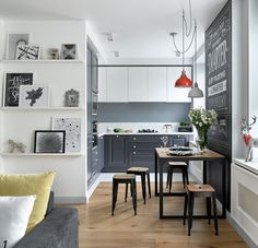 Scandinavian Kitchen with grey cabinets, chalkboard wall and photo ledges