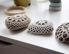 Crochet covered rocks as pattern weights.  Sometimes context changes everything--I never thought of using rocks this way.  From Brett Bara's home studio tour.