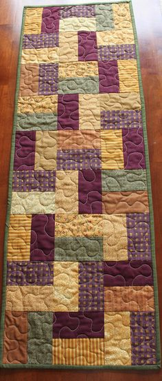 This beautiful fall quilted table runner was created with various fall fabrics. The fabrics feature leaves, fall flowers, plaids, stripes, solids and various patterns in burgundy, purple, green, yellow golden yellow and brown. The warm colors are perfect to brighten up your table