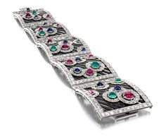 Art Deco Diamond, Enamel, and Gem-Set  Bracelet by Boucheron (Paris, 1925)    Composed of five openwork black enamel and diamond plaques set with cabochon rubies, sapphires, and emeralds; mounted in platinum, osmium, and gold, with French assay marks
