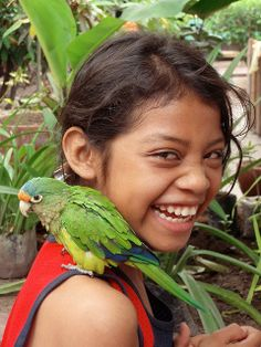 Many birds can be discovered in Nicaragua. Here is a girl interacting with a small parrot. The connection between animals and people is very loving and beautiful.