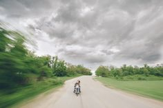 Couple rides a bike through stormy clouds during a Baltimore engagement session with Ben Lau Photography.