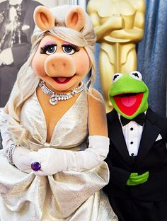 Miss Piggy at the 2012 Oscars, wearing a custom dress by Zac Posen, Christian Louboutin shoes and Fred Leighton jewelry. Hair by Kim Kimble. Her best accessory, however, was her date—Kermit the Frog, who looked handsome in a Brooks Brothers tuxedo. What a cute couple!