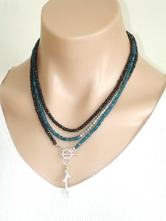 CLICK HERE TO BUY: www.etsy.com/... Ashira Black Spinel and Neon Blue Apatite Gemstone Necklace with Charms. $485.00, via Etsy.