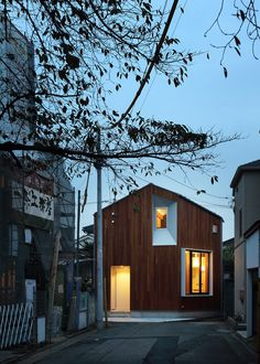 House by Atelier KUKKA is located on a Tokyo street featuring a cherry blossom tree