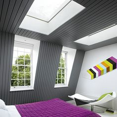 Fantastic color, as well // In this attic bedroom, a mansard roof provides better head height than a traditional loft extension. Tall windows and extra-large skylights maximize the airy feel.