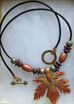 """I made this today for a gift. We don't have maple leaves around here, but I made a """"mold"""" from clay when I lived in Nebraska. I use the mold for the leaf and enhance it with beautiful fall metallic colors. Most of the beads are also made with clay. Look for items for sale on www.etsy.com/shop/hookedonclay"""