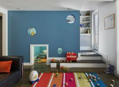 """from site:  As for the garden-level floor, Brendan says, """"The space at the bottom of the stairs is a kids' playroom—the odd leftover space under the stair was turned into a playhouse—with portholes and a small tunnel for toy trains and toy horses."""""""