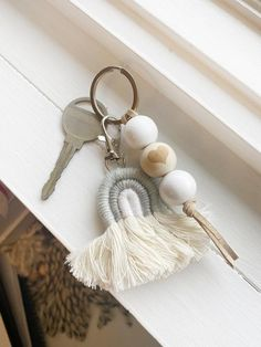 """This Mini Gray & White Boho Neutral Rainbow Keychain is so adorable.  With a woven rainbow attached to all natural wood beads on a key ring. White painted beads and one all natural wood bead with a heart on leather string makes for a great keychain you can't lose in the bottom of your bag!This is a mini rainbow!  1.5x2.5 it attaches on our key rings.  The wood bead keychain is 5"""" long with 20mm wood beads.  Gift yourself today or someone you love!  Cute also as a zipper pull on a bag.See mor Wooden Keychain, Cute Keychain, Bead Keychain, Keychain Ideas, Tassel Keychain, Leather Keychain, Rainbow Wood, Macrame Patterns, Bead Crafts"""