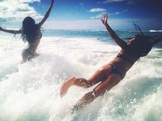 Jumping over beach sea waves with friends