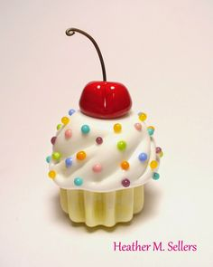 """""""Sweet Tooth""""  A flamework glass cupcake paperweight made by Heather Sellers."""