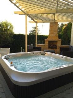 New Jacuzzi J400 series spa with fireplace in the background.