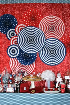 Fourth of July Dessert Table! Adorned with Red, White & Blue candy from the Candy Warehouse and Red, White & Blue gum balls and candy cups from The Tom Kat Studio. Beautiful Fourth of July paper fans highlighted our backdrop, along with adorable 4th of July Party Crackers from Pimlott & Co.